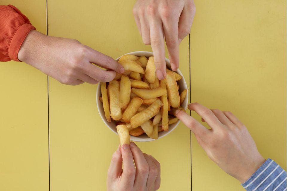 Food Trend: Hände greifen nach Pommes