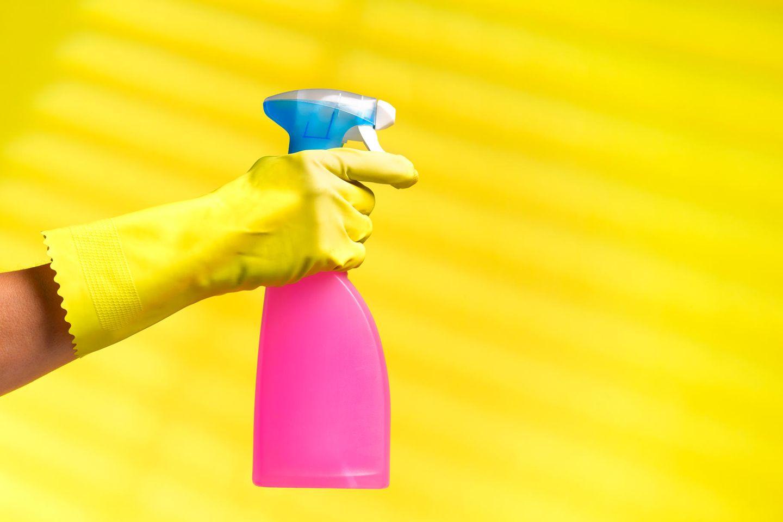 Sprühflasche und Putzhandschuh vor gelbem Hintergrund