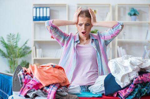 Frau verzweifelt vor Bügelbrett