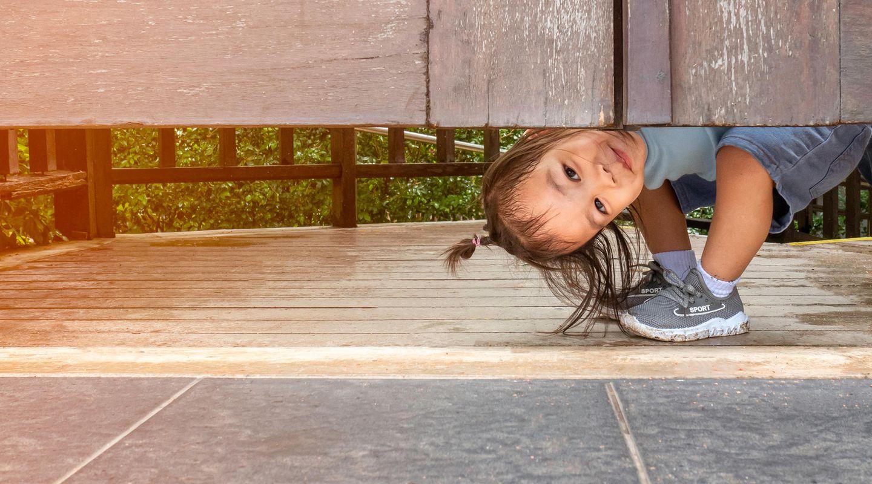 Verstecken spielen: Kind guckt hervor