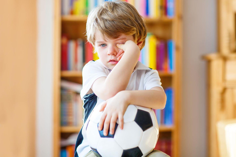 Kita-Vertrag : Unglücklicher Junge mit Ball