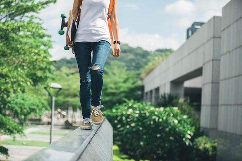 Wie kann ich mir mein Leben leichter machen? Eine junge Frau balanciert auf einer Mauer