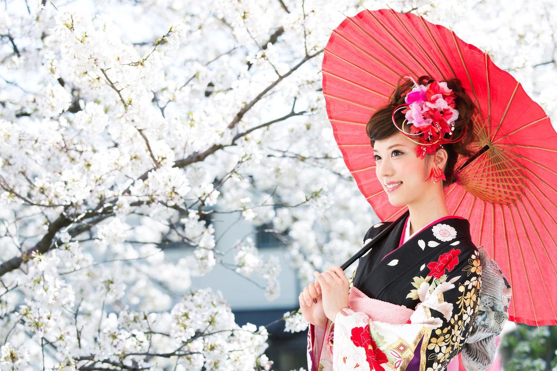 Anti-Stress-Tricks aus Japan: Eine japanische Frau mit Schirm vor einem Kirschbaum