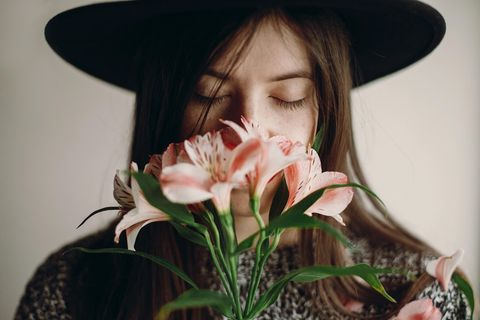 Anti-Komplimente: Frau mit Hut riecht an Blumen
