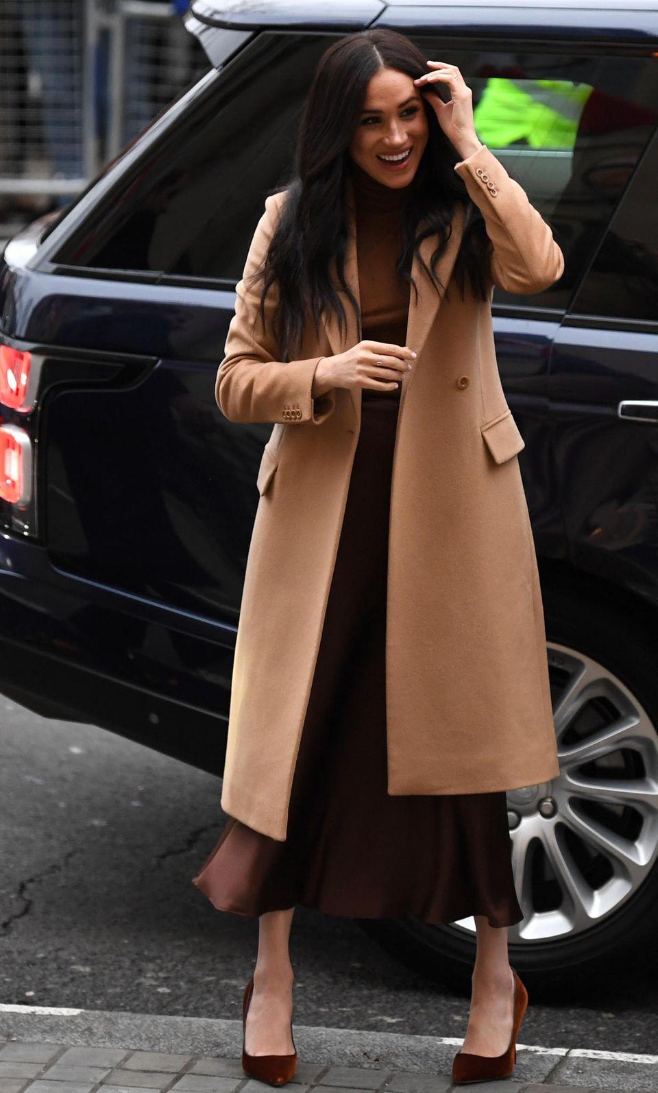 Den kalten Januar-Temperaturen trotzte Meghan Markle in einem klassischen Camelcoat. Der braune Turtleneck sowie Slipskirt waren die perfekte Ergänzung.