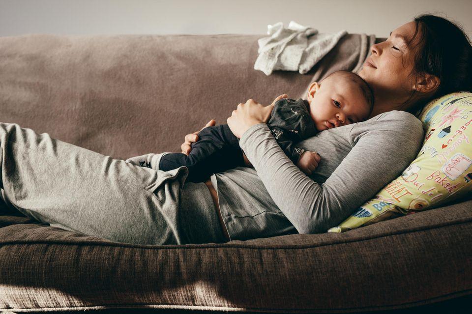 Sätze, die Du vermeiden solltest: Mutter liegt mit Baby auf dem Sofa