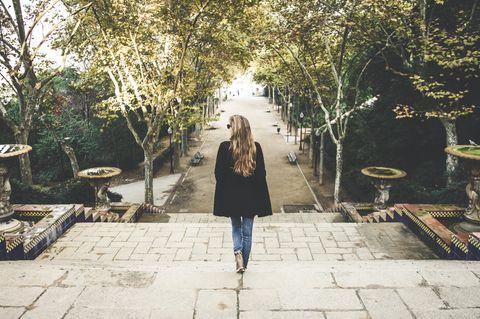 Woran erkennt man unsichere Menschen? Eine gut gekleidete Frau auf einer Treppe