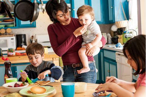 Mutter mit drei Kindern beim Frühstück
