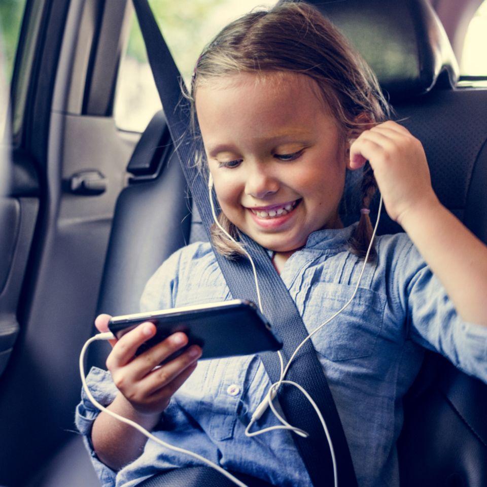 Mädchen sitzt im Auto und hält Smartphone in der Hand