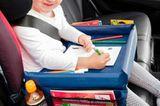 Mädchen sitzt im Auto mit Knietablett