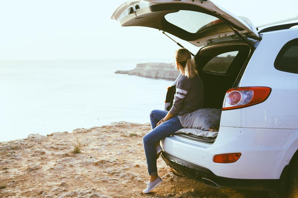 E-Auto: Eine Frau chillt im Kofferraum ihres Autos am Meer