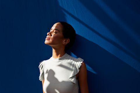 Frau vor blauem Hintergrund mit Gesicht zur Sonne