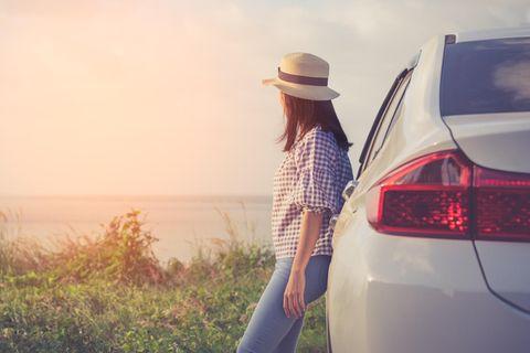 Umwelfreundliches Autofahren: Frau lehnt an Auto und schaut aufs Meer
