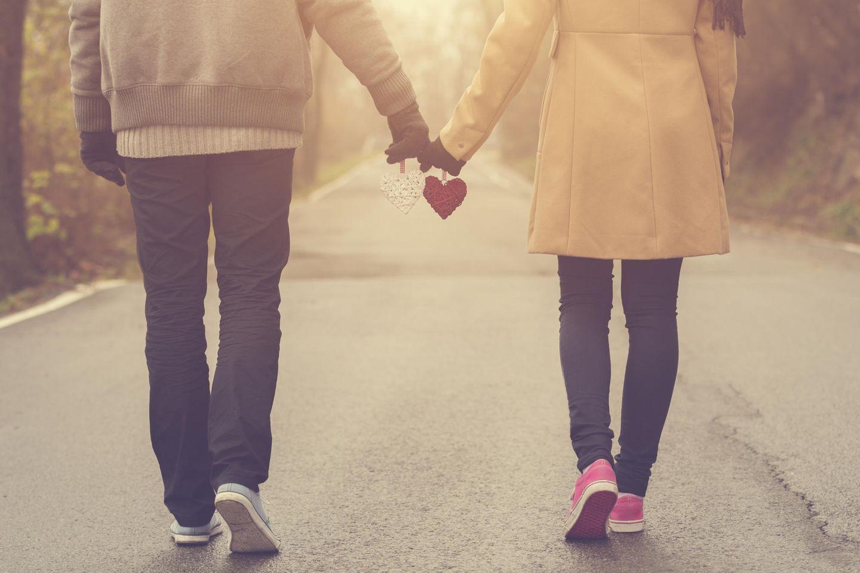 Woran glauben glückliche Paare? Ein Paar geht Hand in Hand spazieren