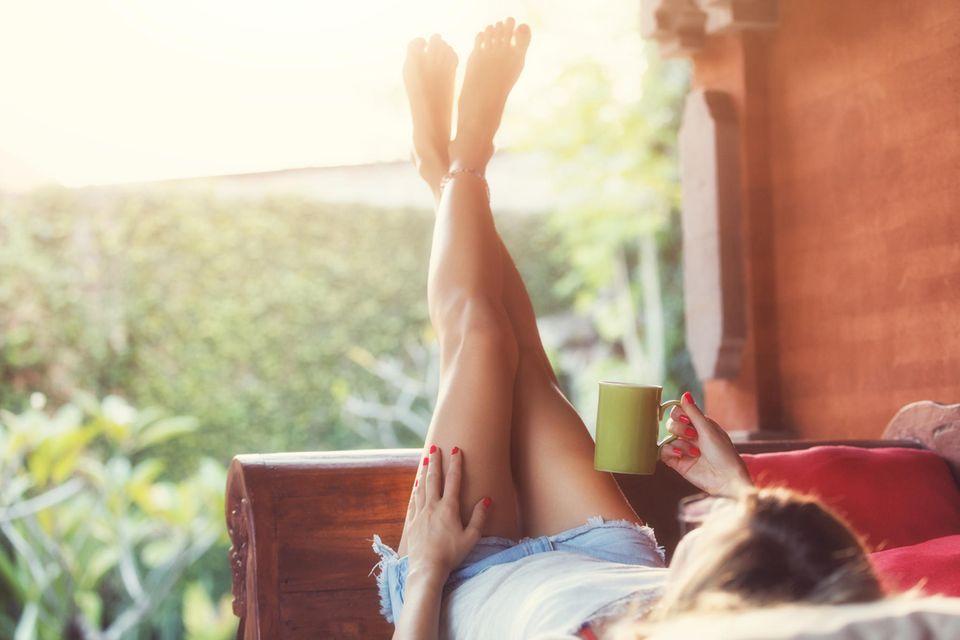 Astrologie: Eine Frau entspannt mit einer Tasse Tee