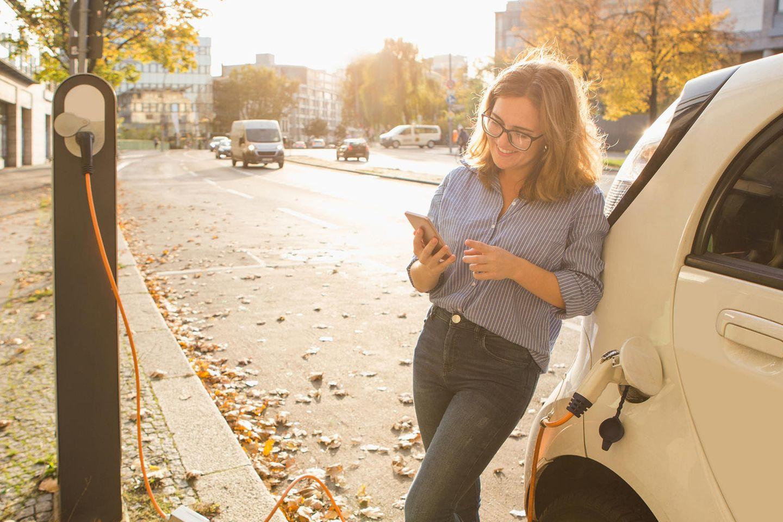 Nachhaltig Auto fahren: Frau lehnt an E-Auto