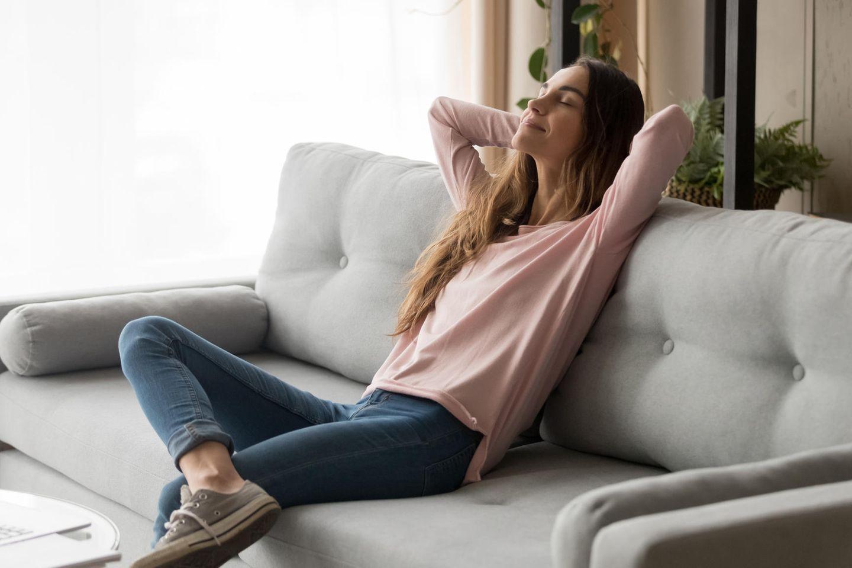 Frau, entspannt auf Sofa