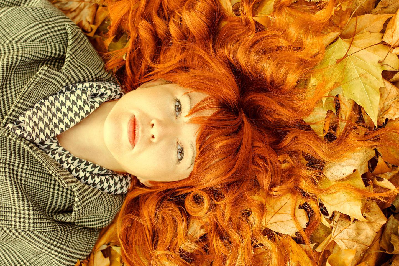 Frau liegt auf Herbstlaub