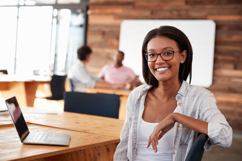 Die besten Arbeitgeber für Frauen - BRIGITTE-Studie klärt auf: glückliche Frau bei der Arbeit