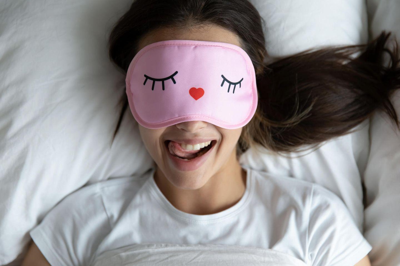Wer um diese Uhrzeit aufsteht, ist glücklicher und verdient mehr: Frau im Bett