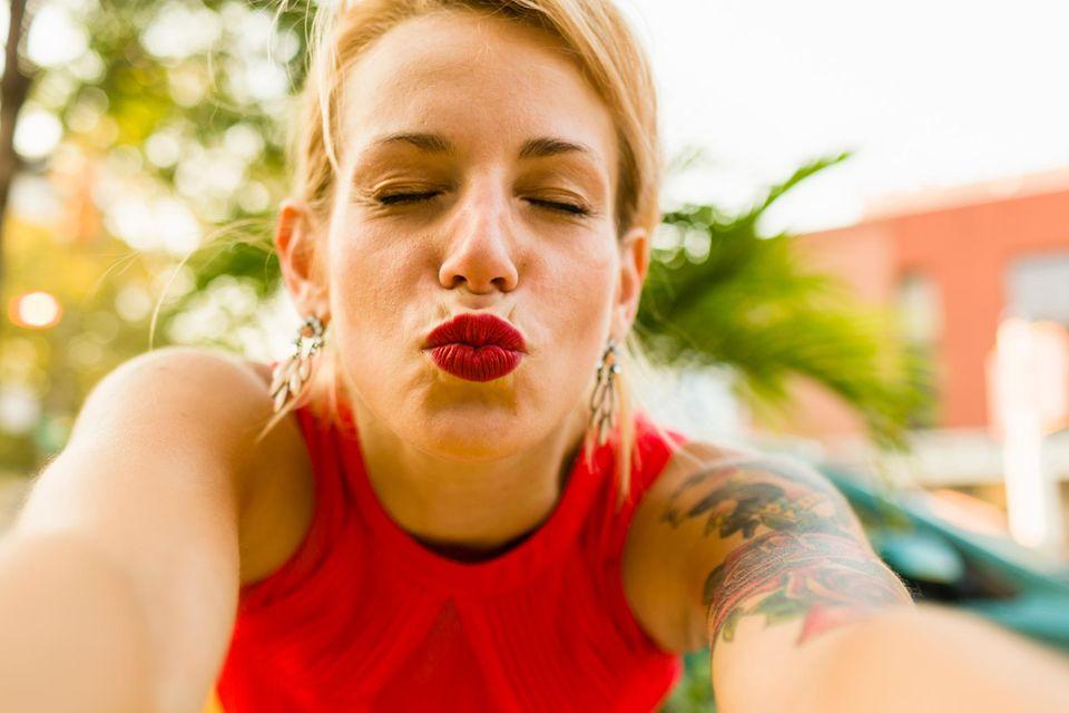 Volle Lippen: Frau macht einen Kussmund