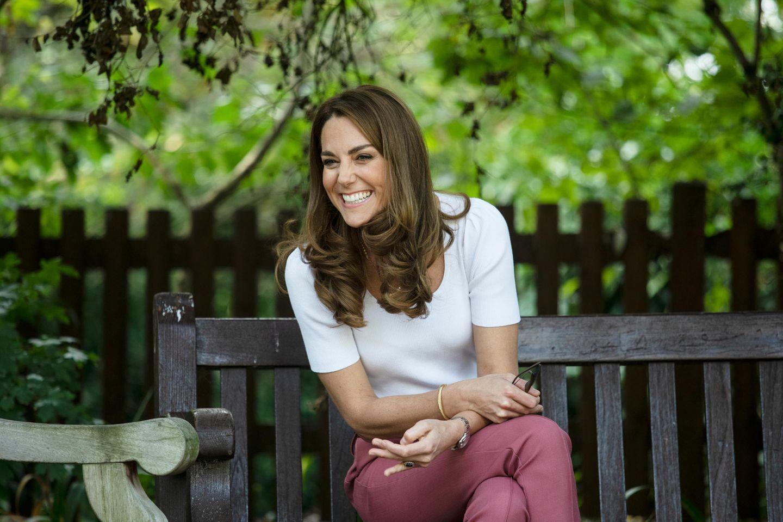 Herzogin Kate: auf einer Bank und lacht