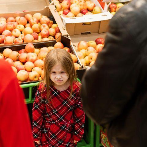 Einkaufen mit Kindern: Eltern mit bockiger Tochter im Supermarkt