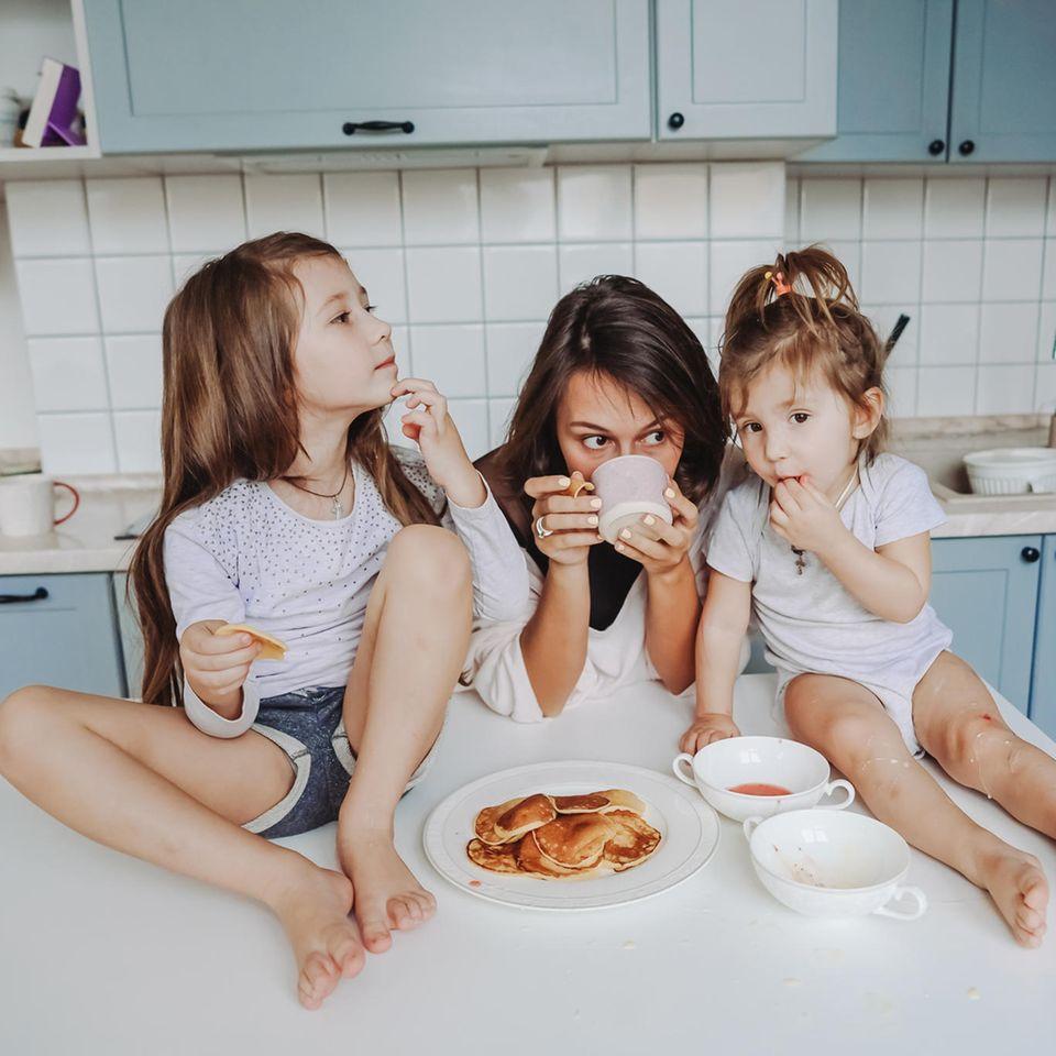 Mental Load: Mutter isst mit ihren zwei Kindern in der Küche