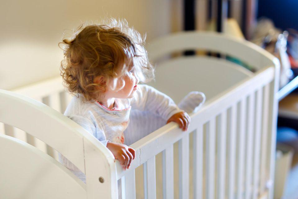Kind schläft nicht: Kind steht im Gitterbett