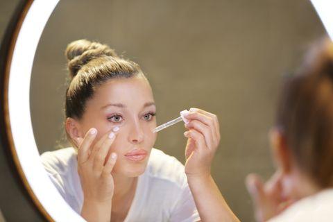 Frau trägt Hyaluron Serum vor dem Spiegel auf die Gesichtshaut auf