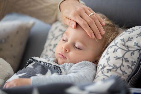 Krankes Kind: Mutter legt die Hand auf die Stirn