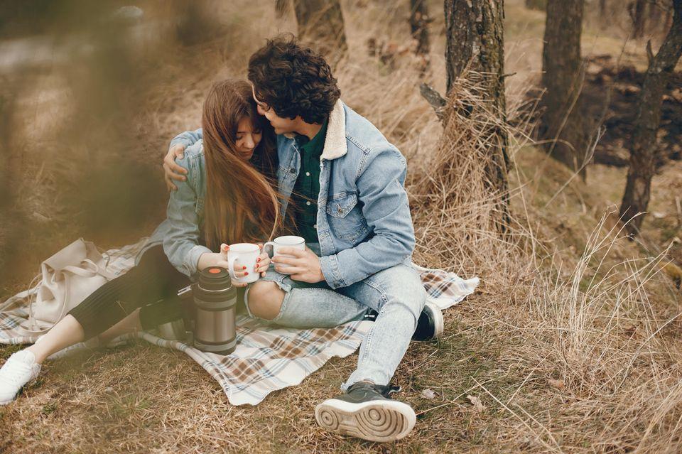 Selbstverwirklichung in der Partnerschaft: Ein Pärchen auf einer Picknickdecke im Herbst