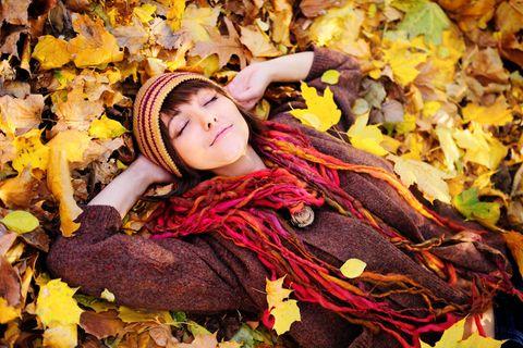 Horoskop: Eine glückliche Frau liegt im Herbstlaub