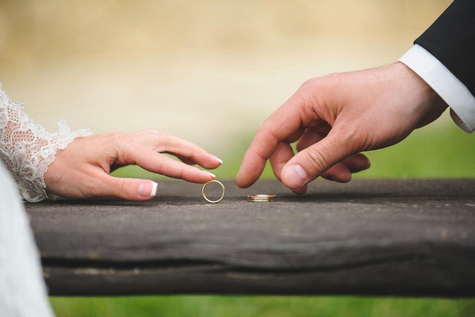 Whisper: Zwei Hände eines Brautpaares mit Eheringen