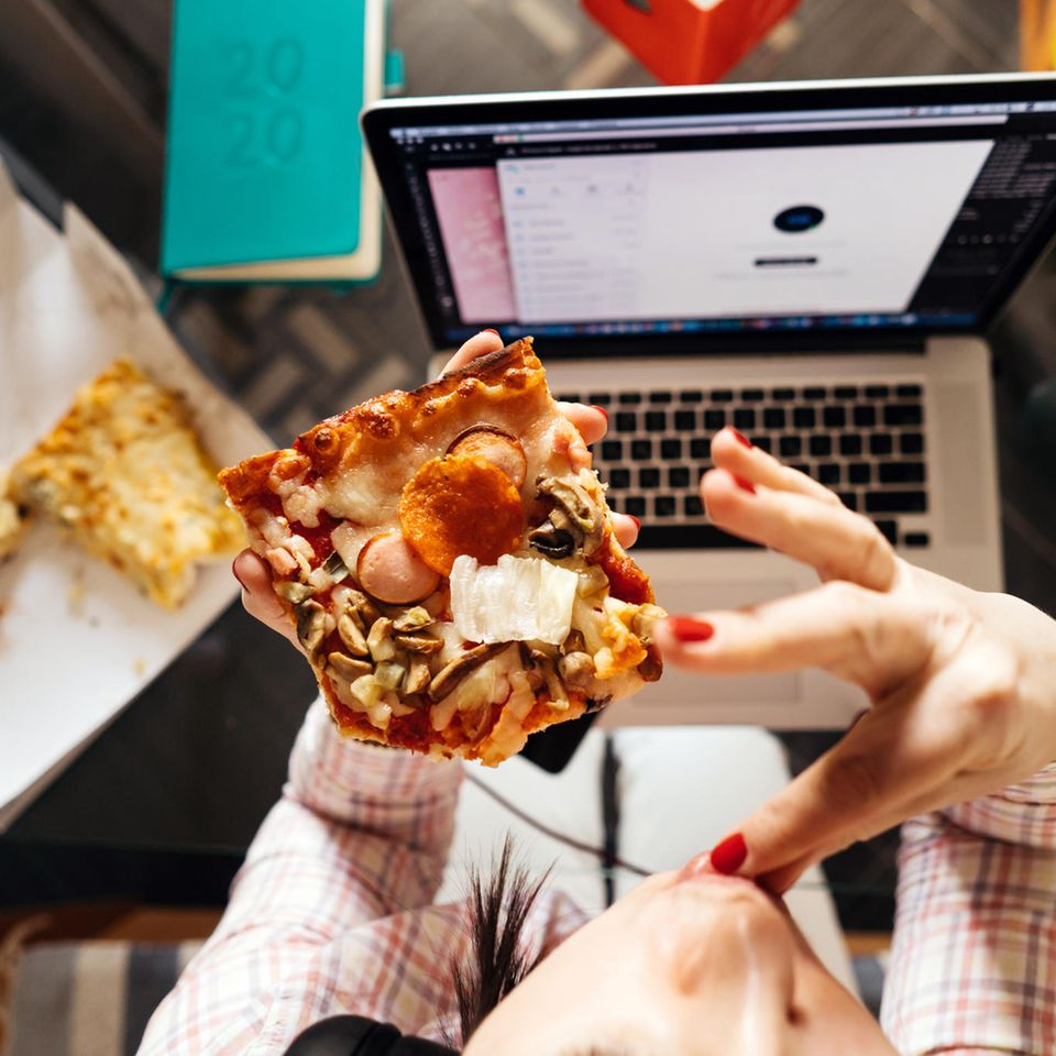 Achtsames Essen: Frau isst vor dem Laptop