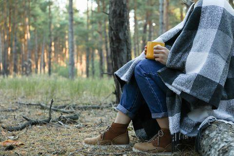 Erfahrungsbericht: Eine Frau mit einer Tasse und einer Decke um die Schultern im Wald