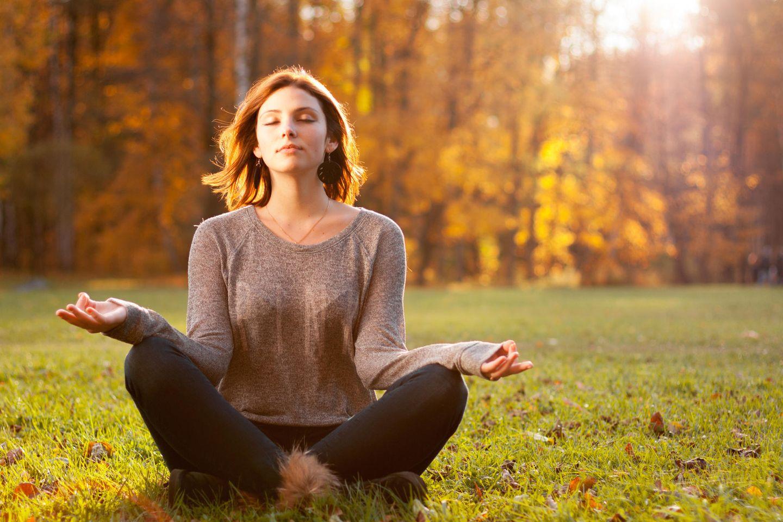 Horoskop: Eine Frau sitzt im Schneidersitz und meditiert