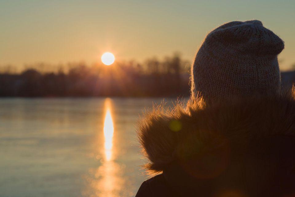 Erfahrungsbericht: Eine Frau schaut sich einen Sonnenuntergang am See an
