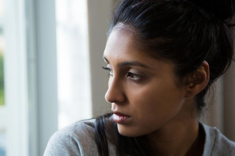 Frauenfeindliche Gesetze: Eine indische Frau schaut traurig aus dem Fenster