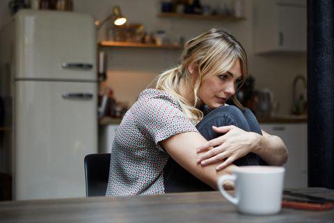 Frau sitzt traurig in der Küche