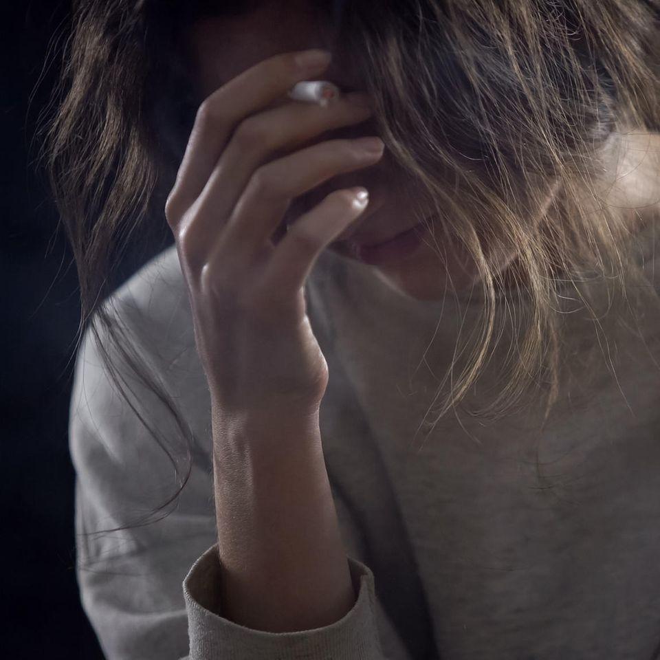 Sexueller Missbrauch: Frau mit Hand vor dem Gesicht