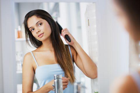 Brünette Frau bürstet sich die Haare vor dem Spiegel