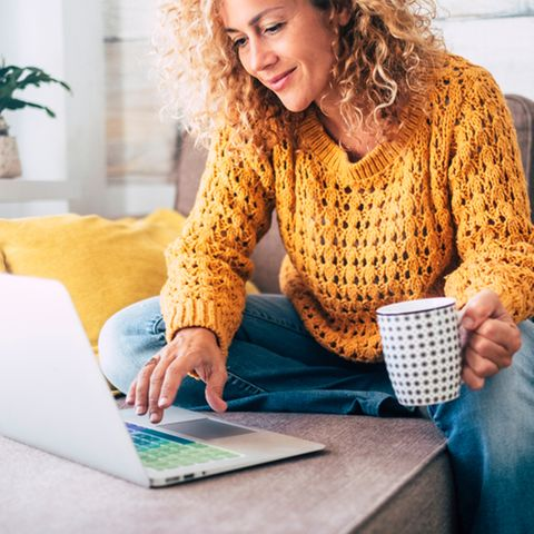Work-Life-Balance: Frau sitzt auf der Couch vorm Laptop