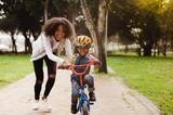 Erziehung: Mama hilft Sohn beim Radfahren