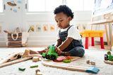 Erziehung: Kind spielt auf dem Boden