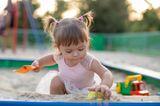 Erziehung: Kleinkind spielt im Sandkasten
