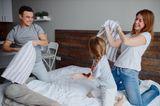 Wer setzt sich durch?: Eltern toben mit Kind auf Bett