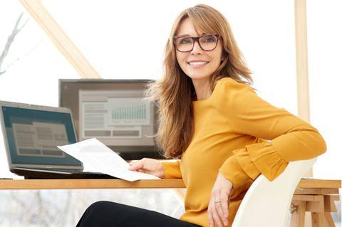 Timeboxing: Frau sitzt lächelnd am Schreibtisch
