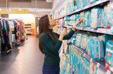 Finanzen: Frau vergleicht Preise beim Einkauf