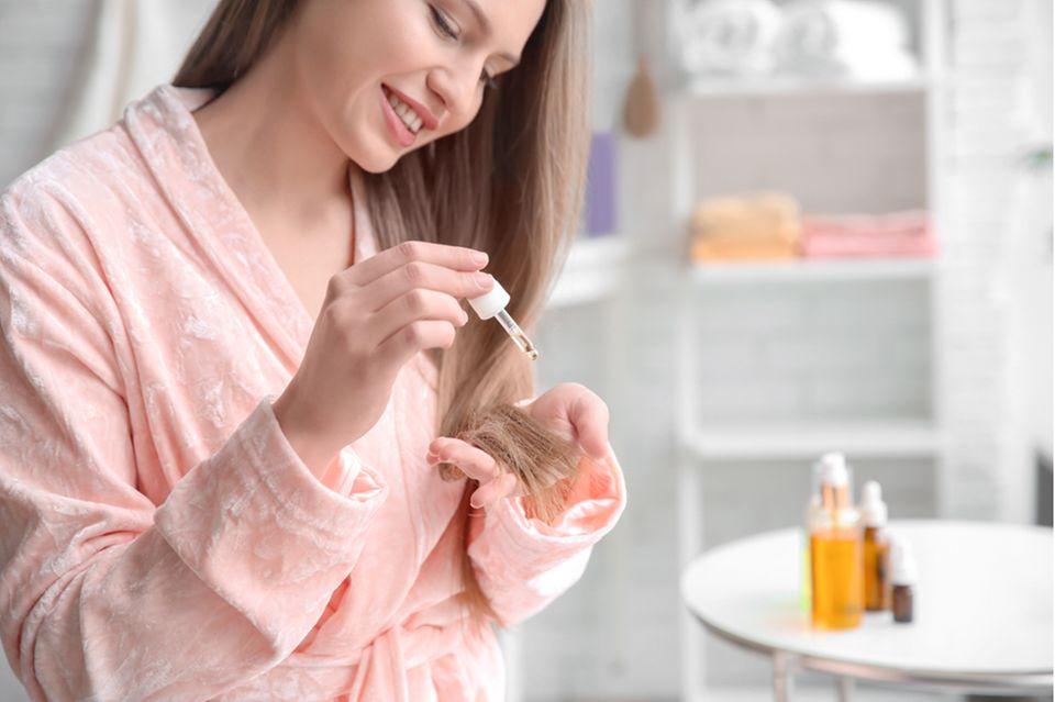 Öl für die Haare: Frau mit langen Haaren hält Ölflasche in der Hand.